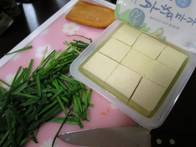 Prepare green onions, chives, and tofu while the soup simmers