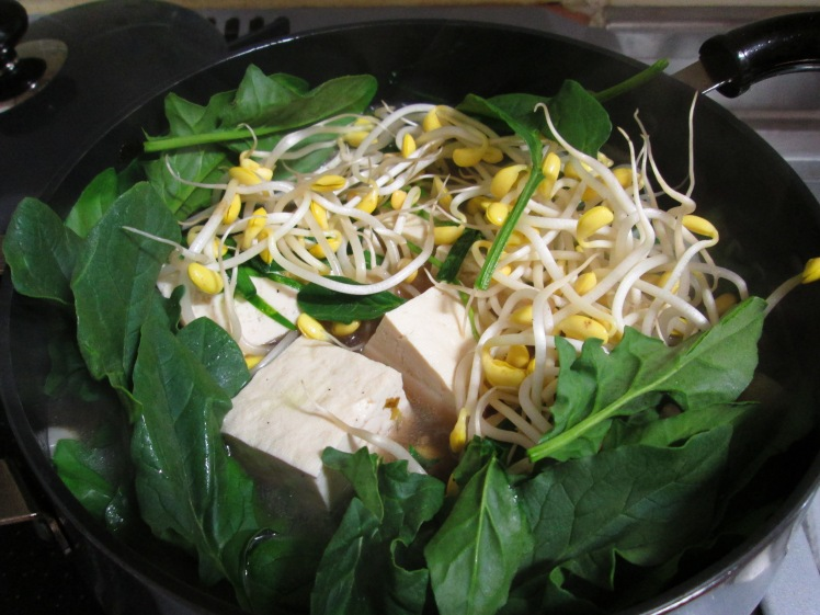 Toss in tofu along with bean sprouts and spinach