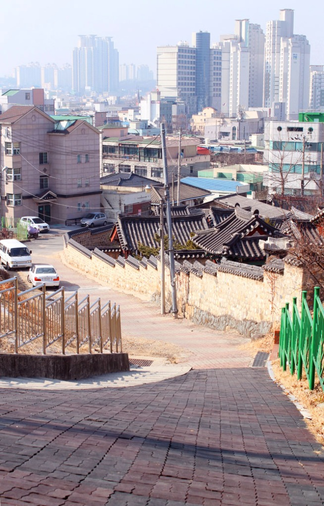 View of skyscrapers with traditional Korean buildings in the forefront.