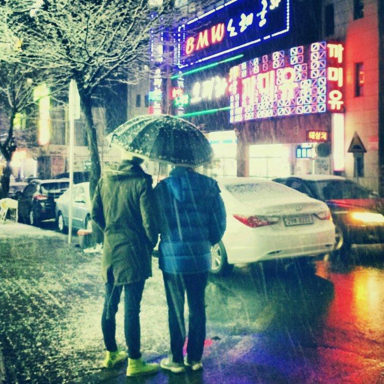 Bros sharing a snow umbrella.