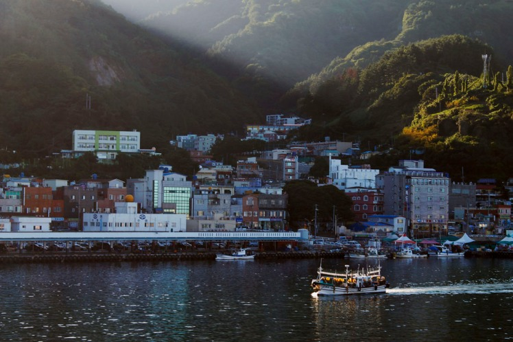 Last rays of the afternoon sun spilling through the valley onto the harbour.