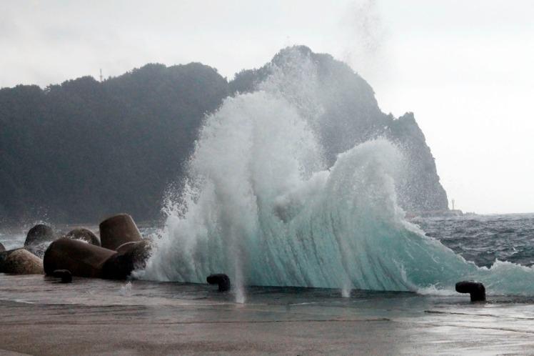 Big wave crashing on concrete pier.