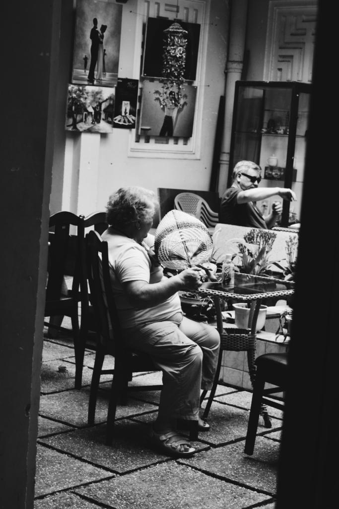 Woman fanning herself in gift shop courtyard.