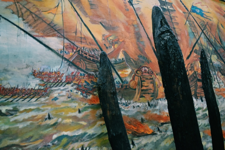 Battle depicted in the background with its preserved wooden masts in foreground.