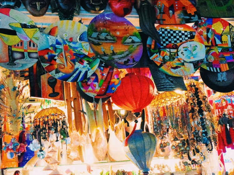 Colourful lanterns and mobiles hanging from a stall.