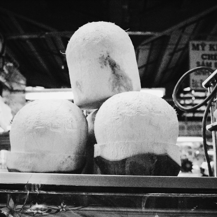 Coconuts ready to be cut open and served with bendy straws.