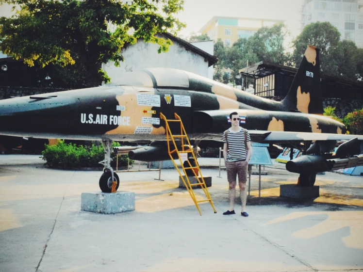 Ricky in front of fighter aircraft located at the entrance of the War Crimes Museum.