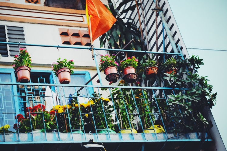 Apartment balcony along flower street bursting with a potted garden of its own.