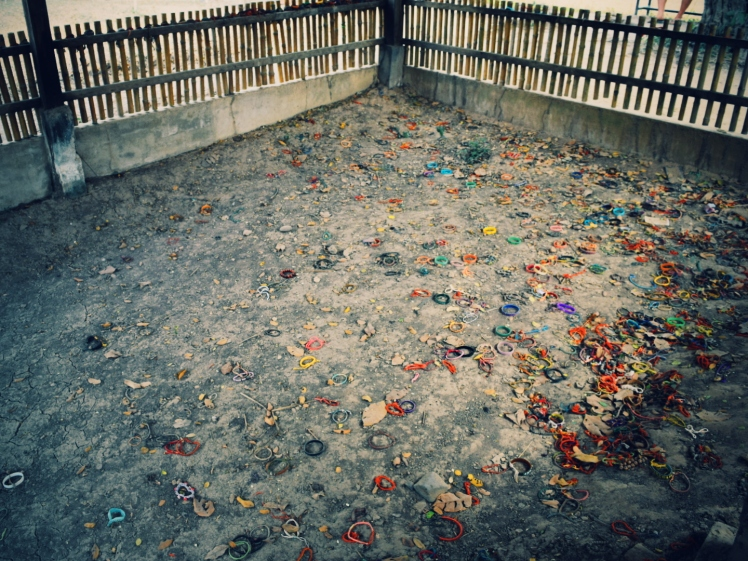 Mass grave with bracelets thrown over in lieu of flowers of remembrance.