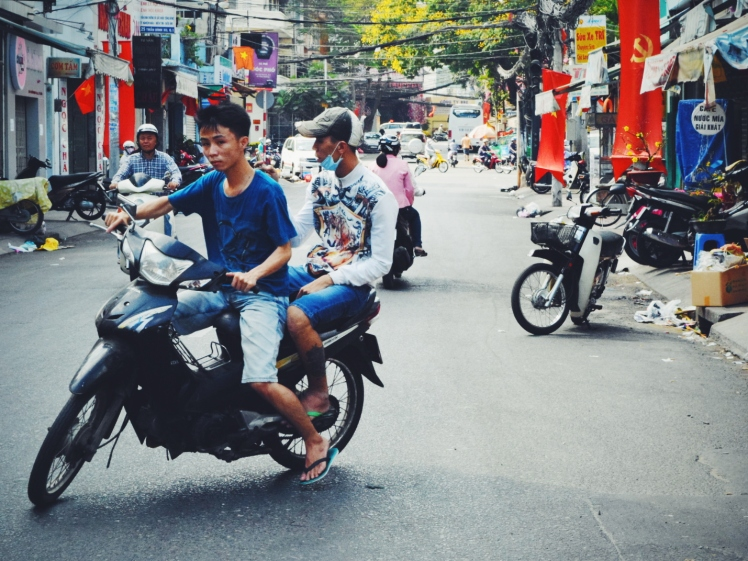 Friends sharing a scooter; communist flags billowing behind them.