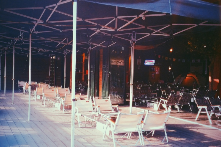 The exterior to Mr. Grill, open air with low chairs around the grills.