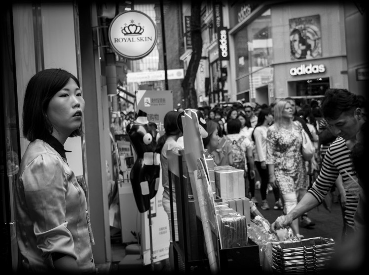 Sales rep watches the crushing throng outside her store. The streets pretty much always look like this.