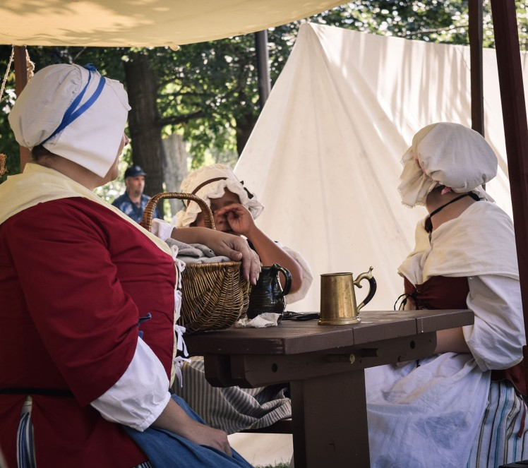 Women in tents dressed in bonnets and skirts.